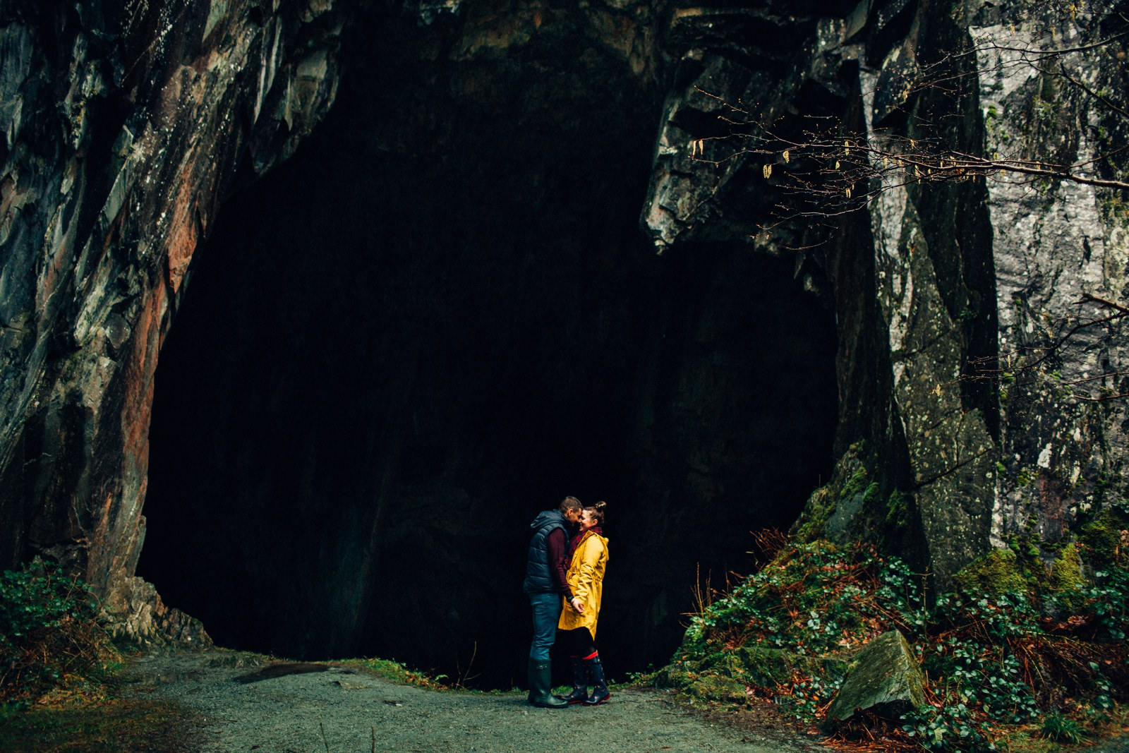 cuddled up couple standing in front of an open cave