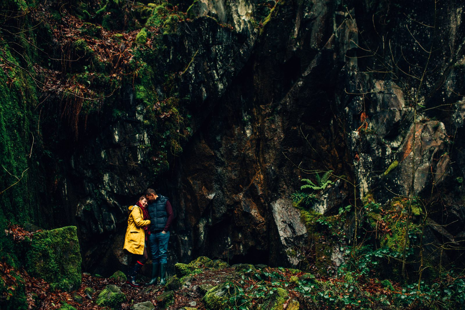 loved up couple standing in front of a dark cave