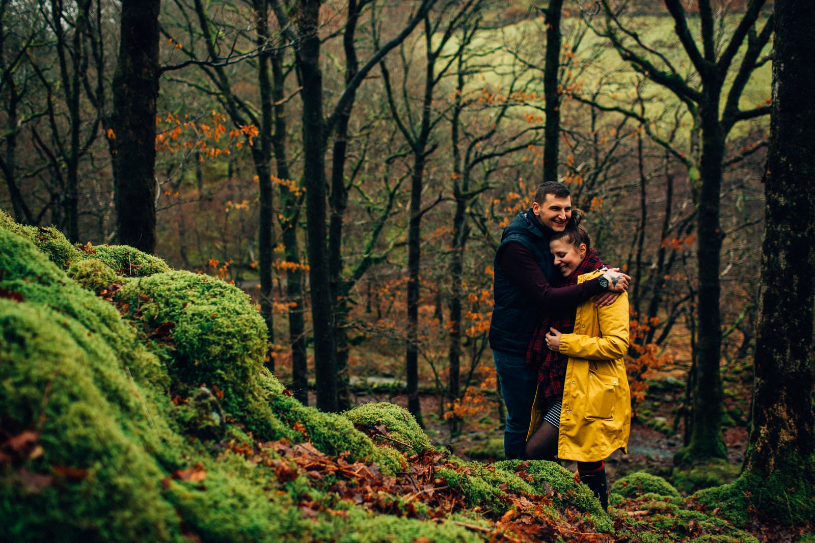 girl and boy standing on mossy ground on top of the hill and cuddling
