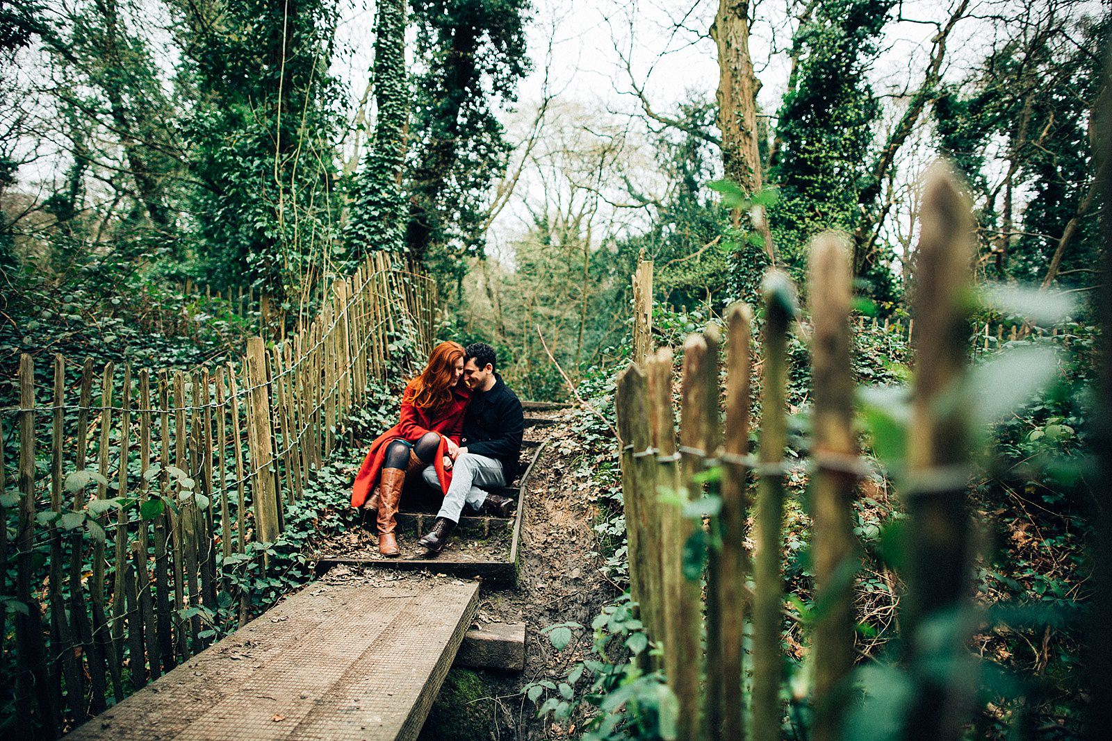 boy and girl sitting down on stairs in the woods cuddling