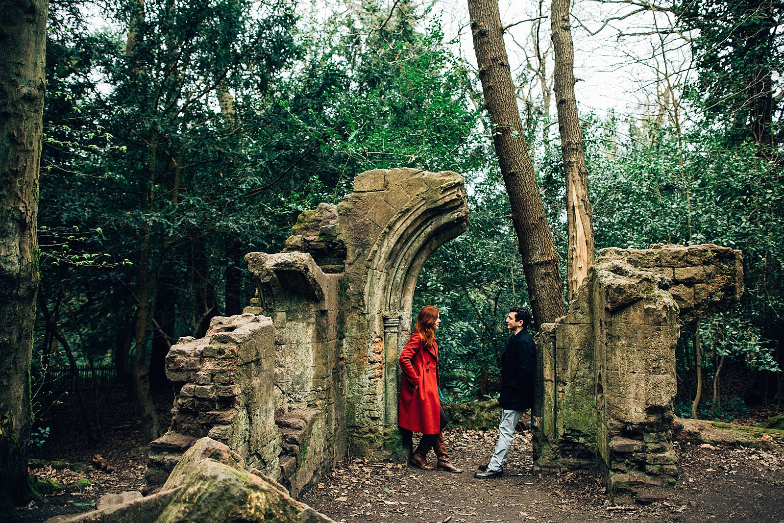 couple standing by the ruins in the woods posing for engagemnt photographer northamptonshire