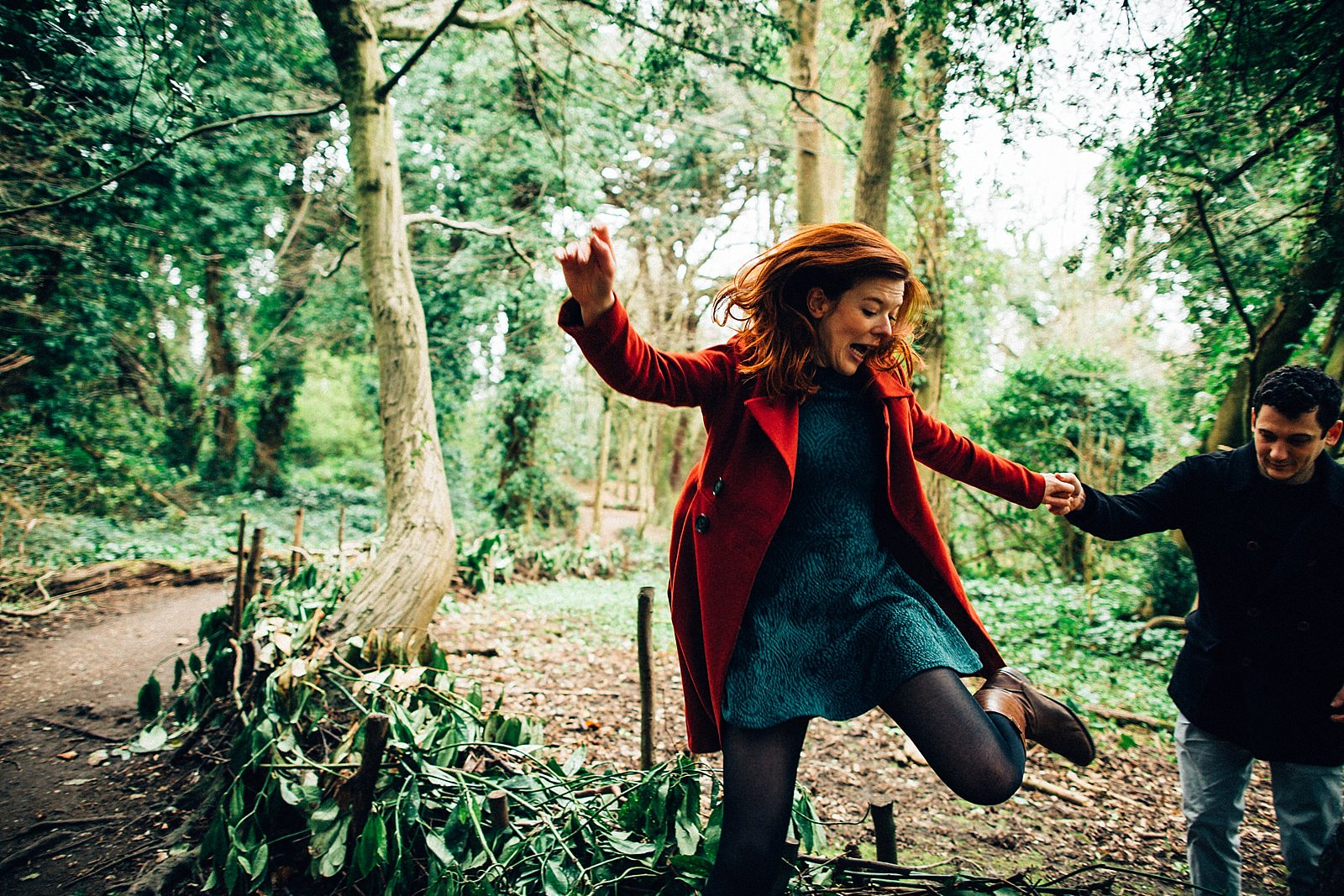 red head girl jumping in the woods