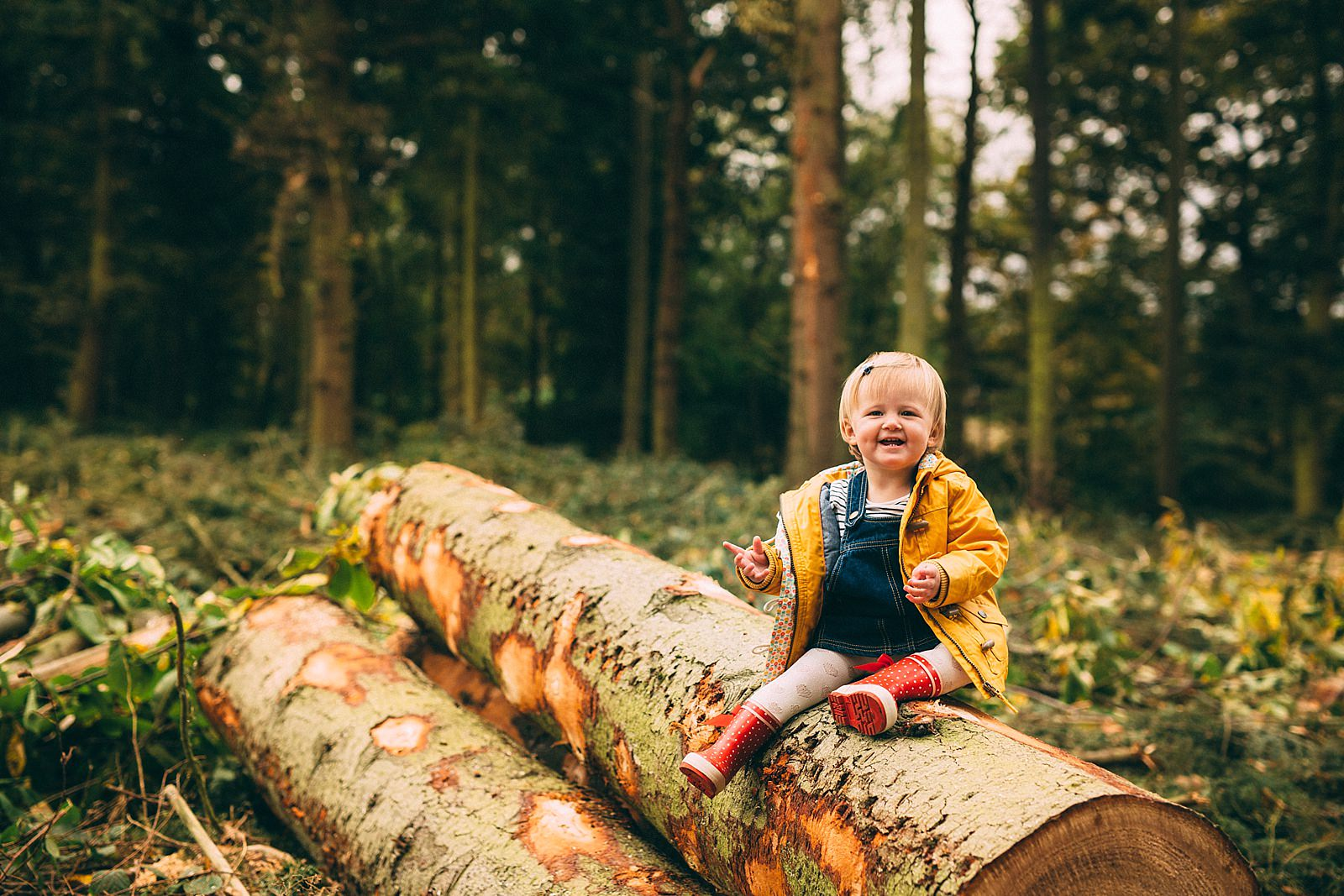 little girl in yellow coat sitting on a wooden log smiling