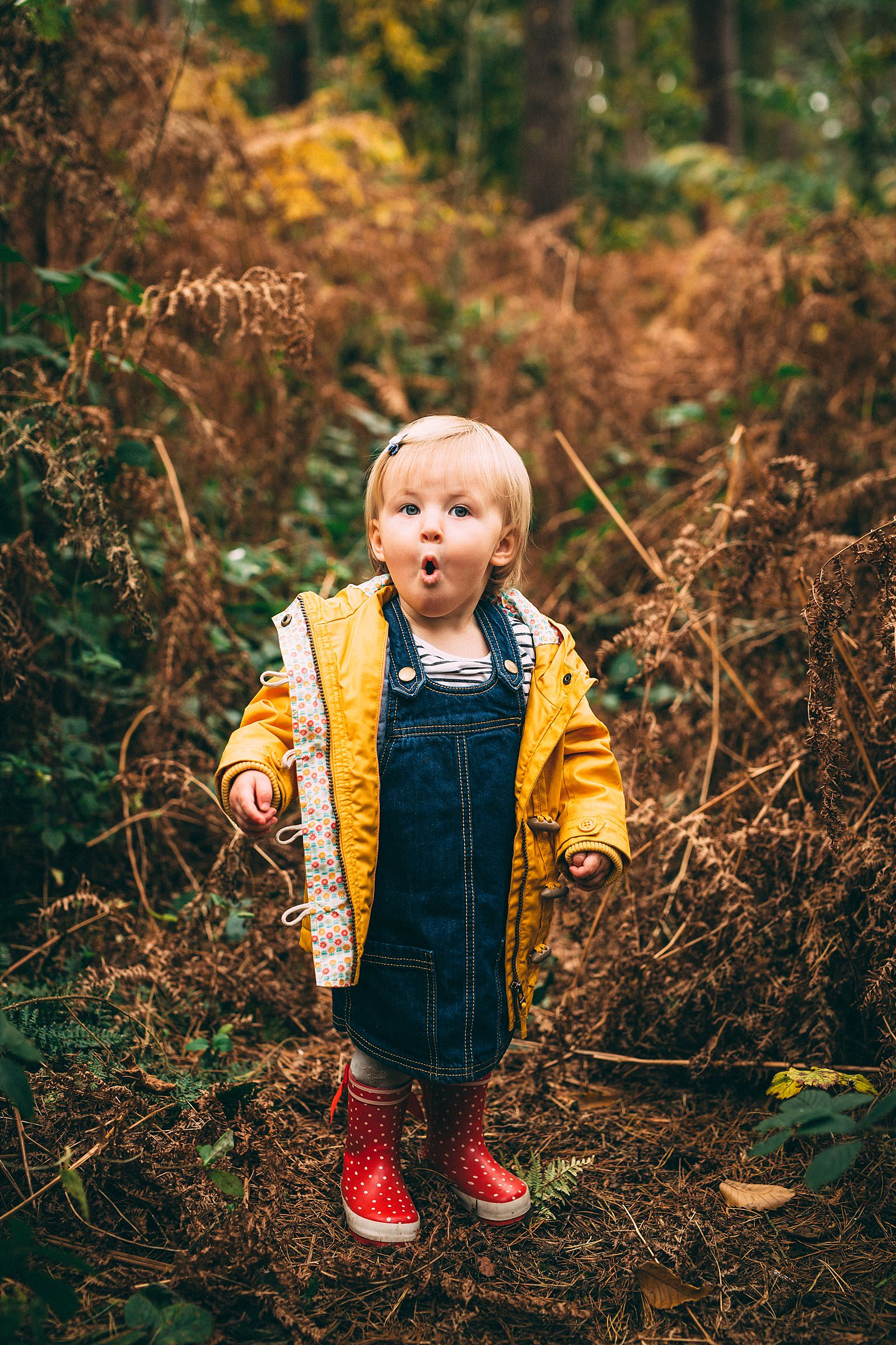little girl in yellow coat standing with mouth open in surprise