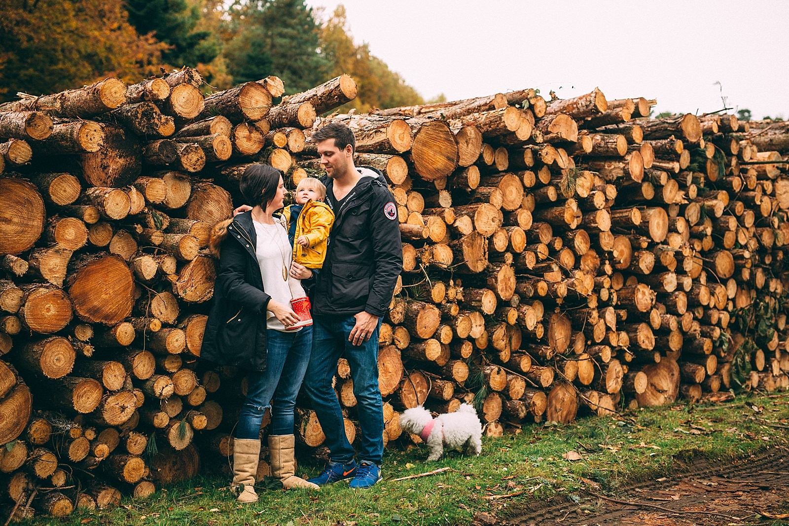 mum and dad holding daughter and standing by wooden logs