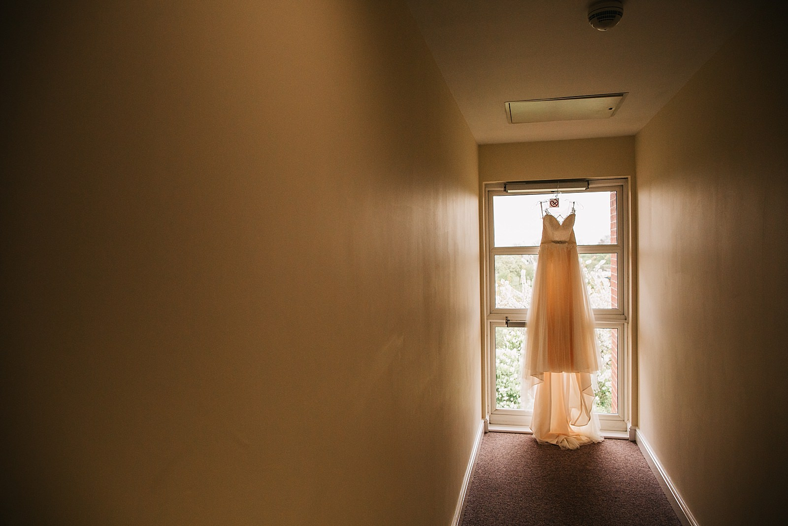 wedding dress hanging on the window
