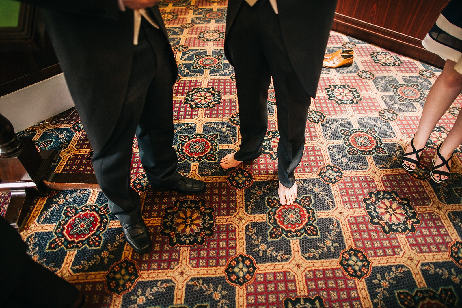 groomsmen without shoes standing on a red carpet