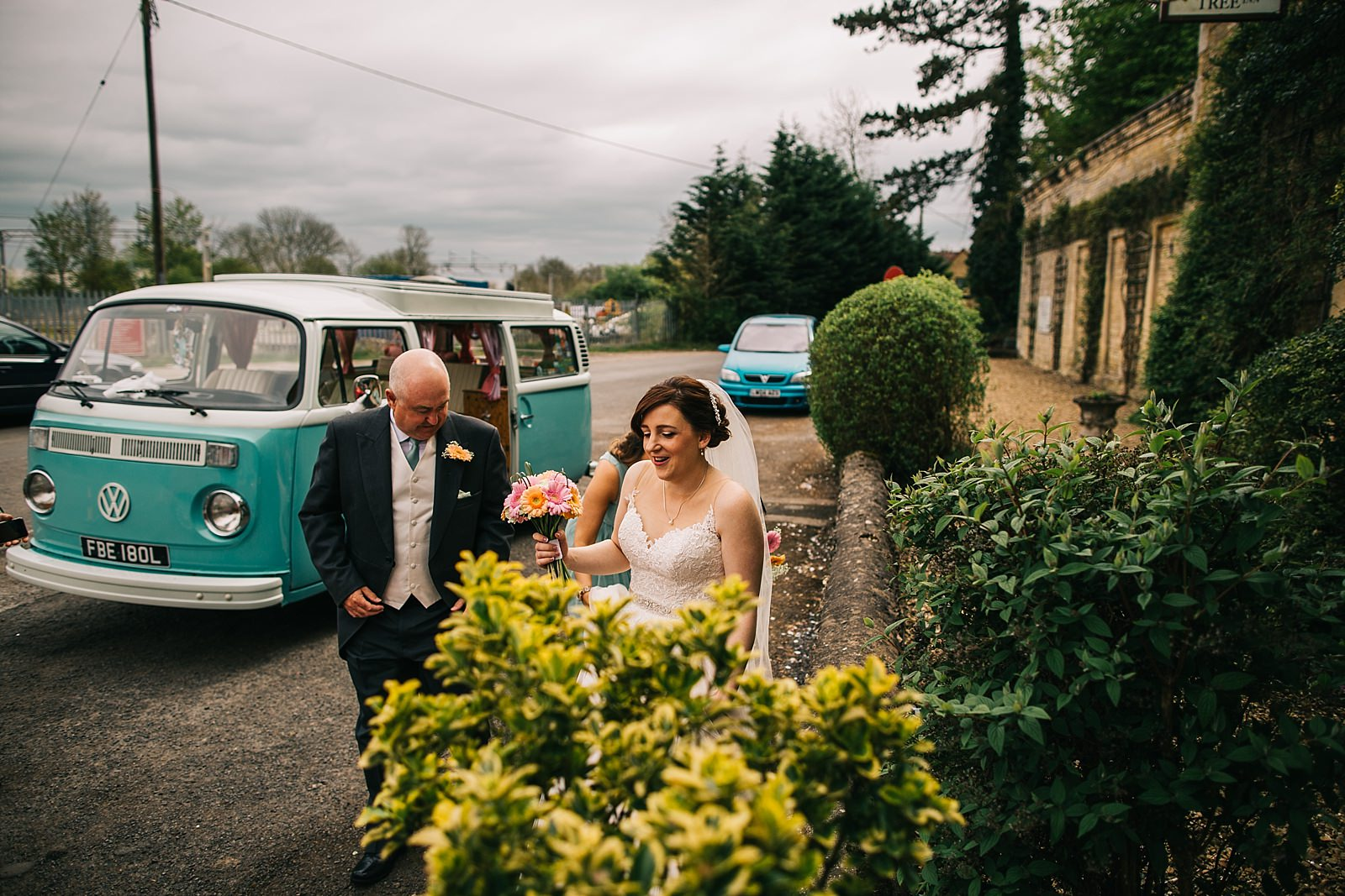 bride and dad walking towards Northamptonshire wedding photographer