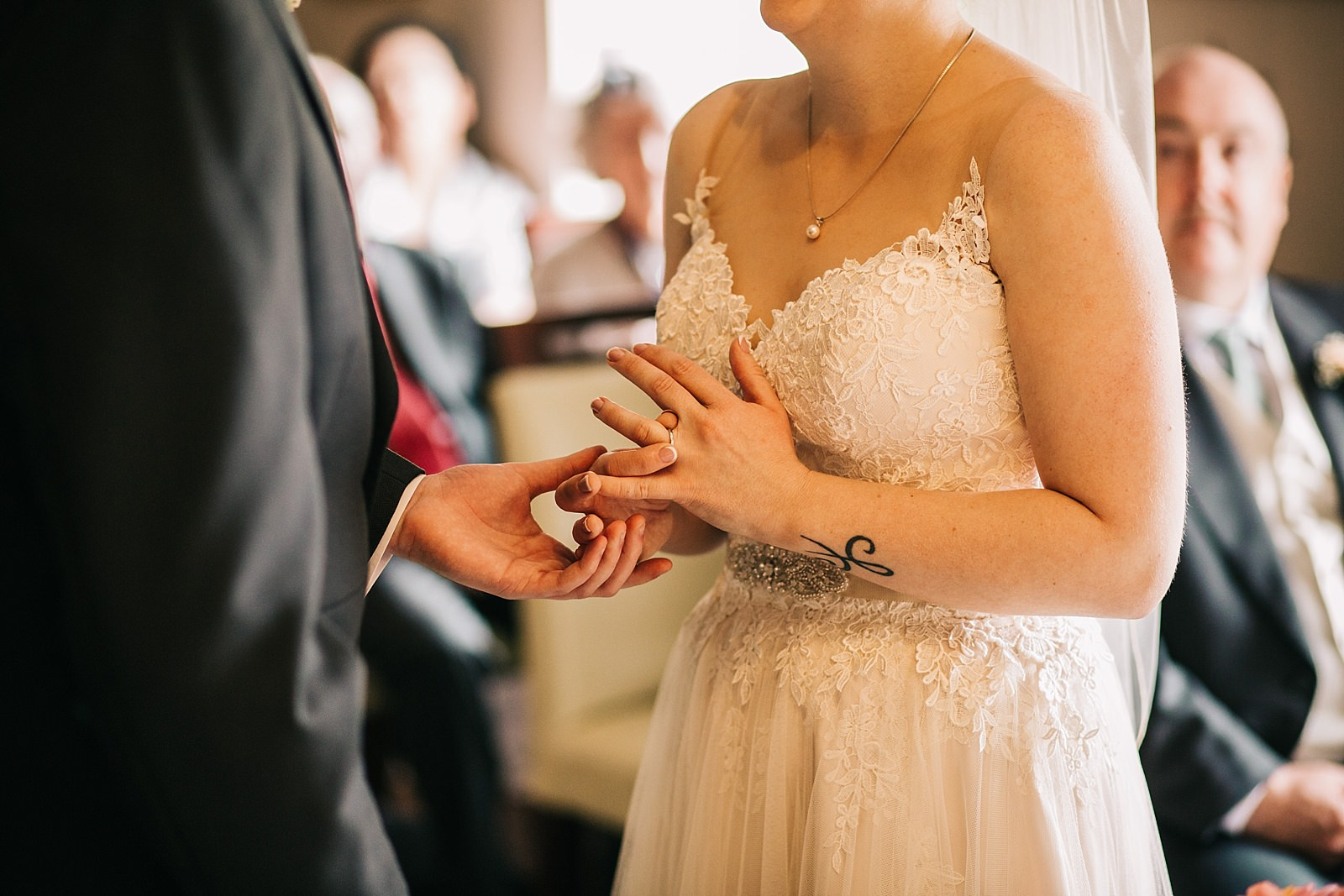 photo of bride trying on wedding ring during ceremony