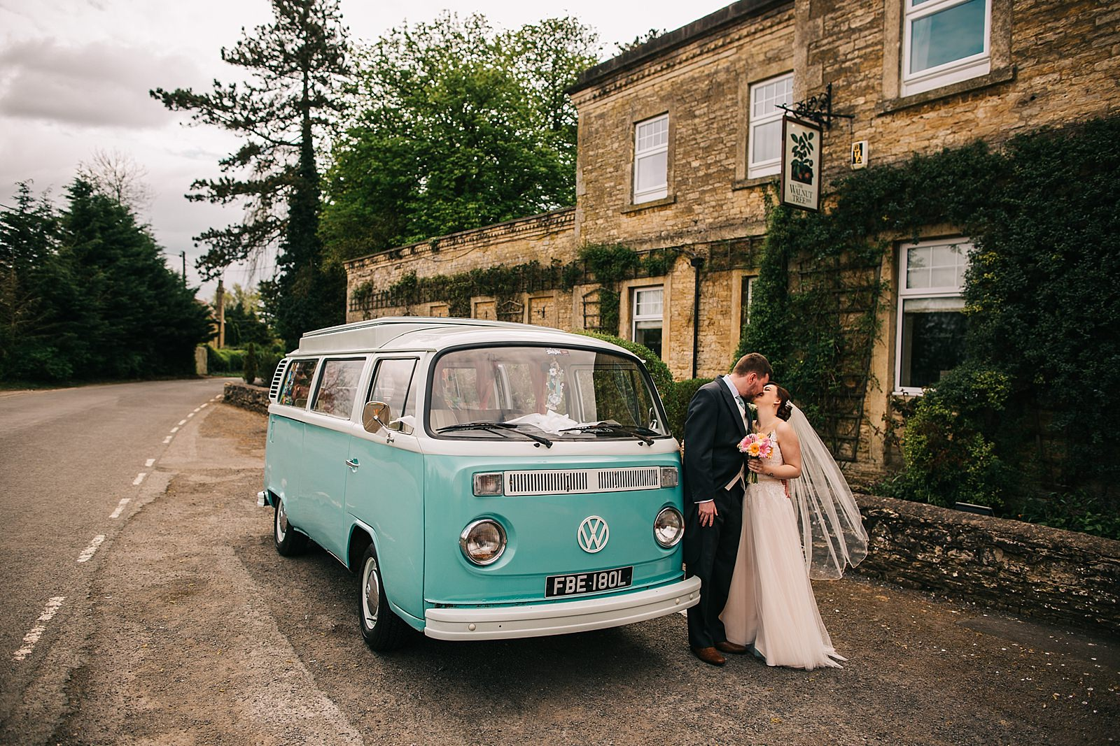 newlywed standing by the camper van photographed by Northamptonshire wedding photographer