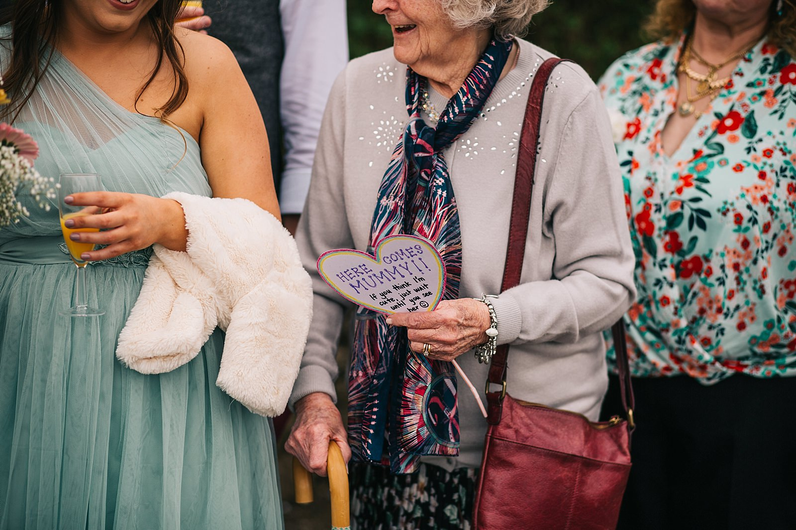 grandmother holding here comes mummy sign