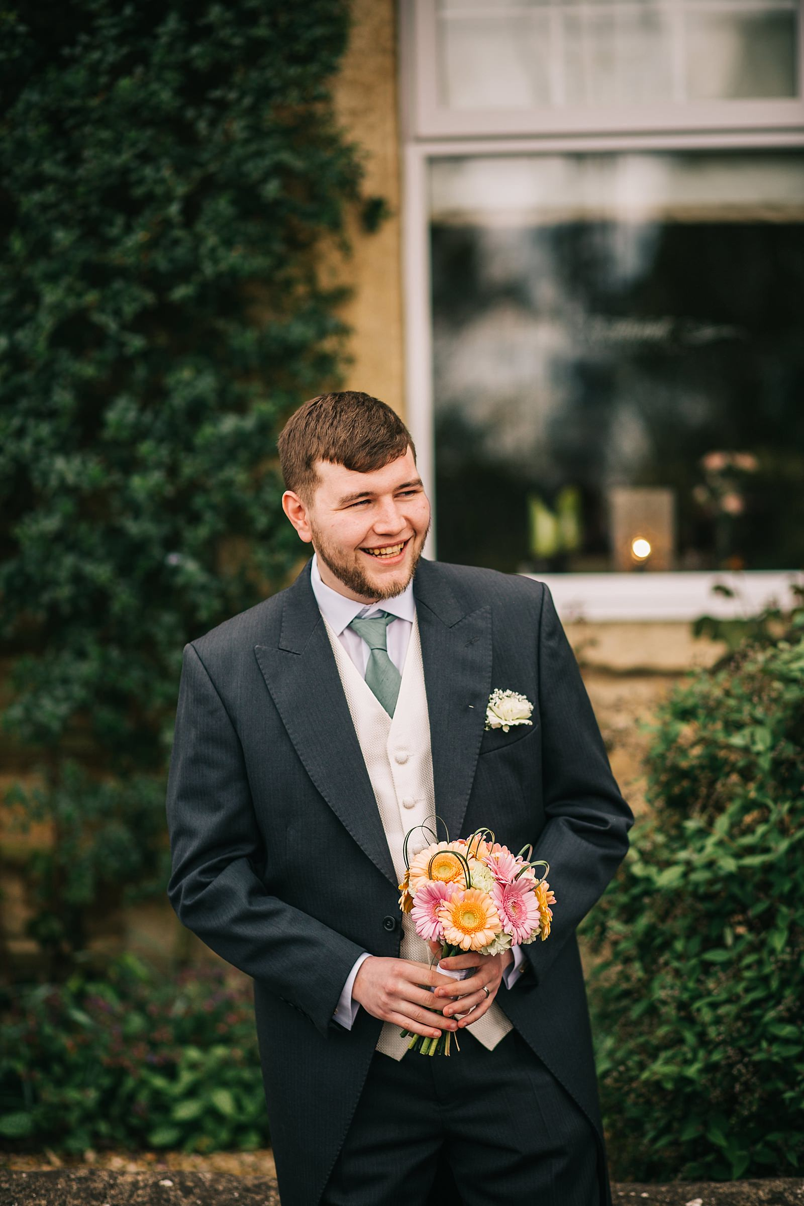 groom holding brides flowers and smiling