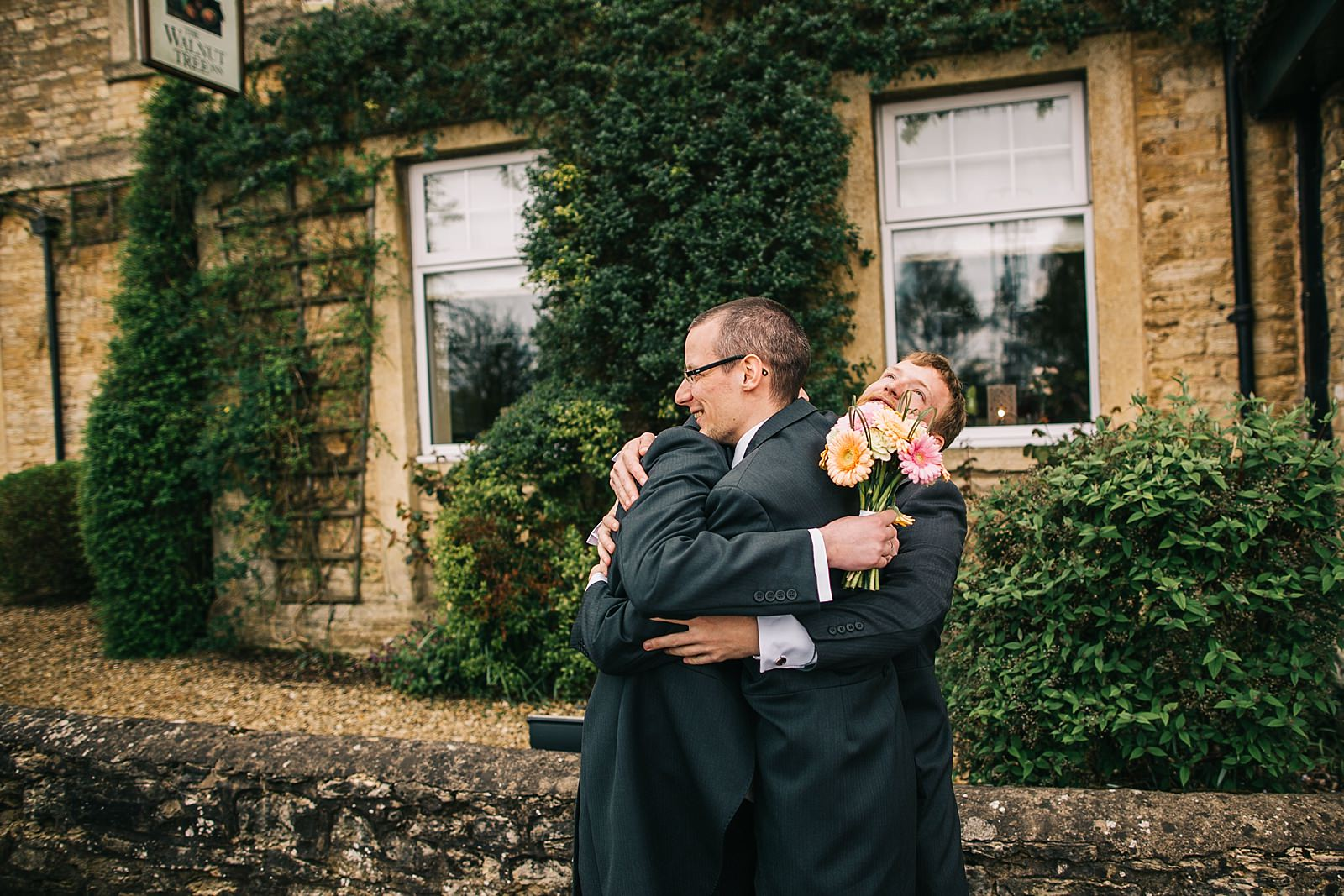 groom hugging groomsmen photographed by Northamptonshire wedding photographer