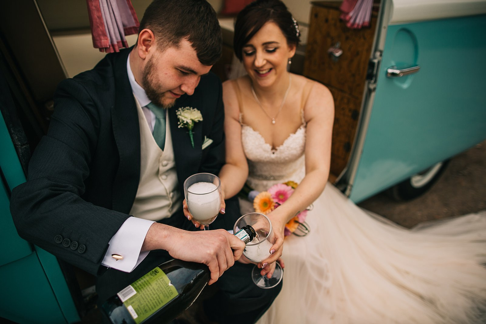 bride and groom drinking champagne in the camper van