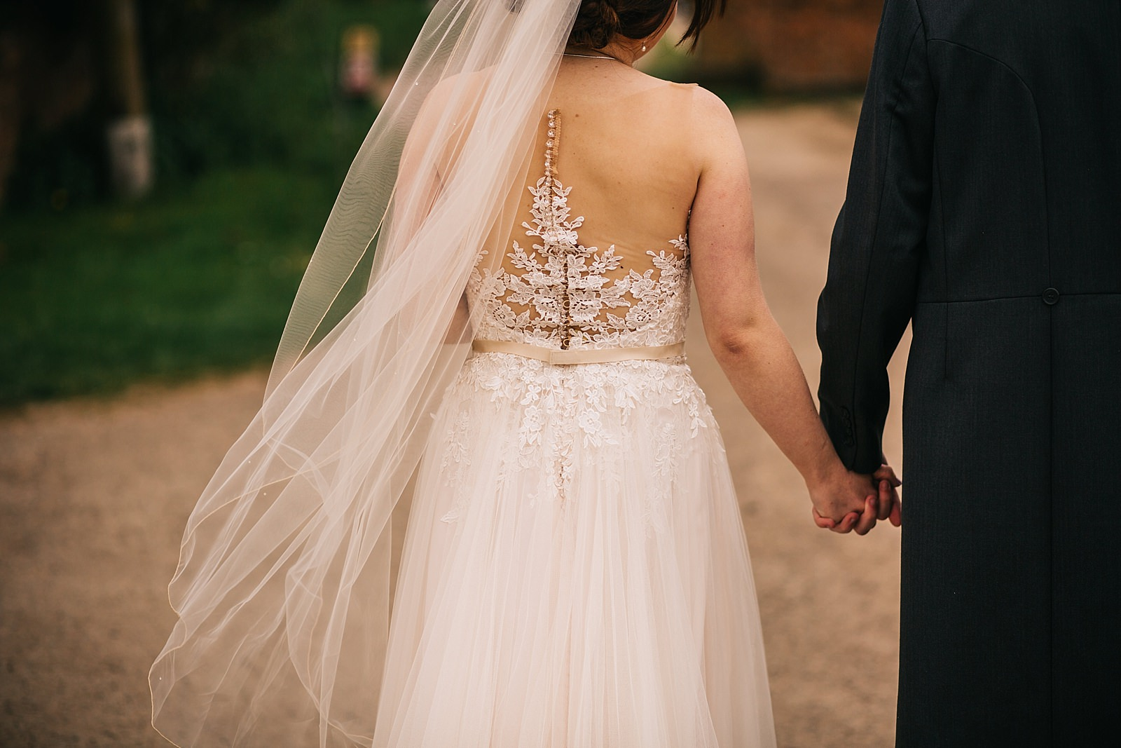 photo of newly wed couple holding hands and walking away