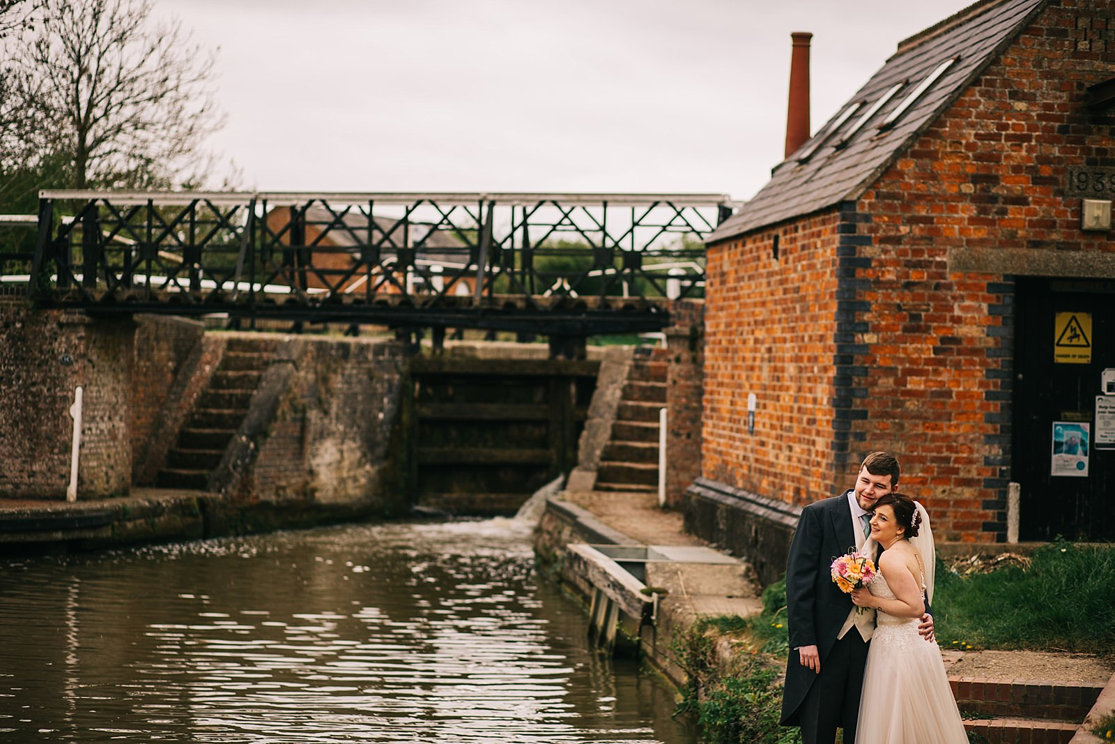 bride and groom standing by the canal being photographed by Northamptonshire wedding photographer