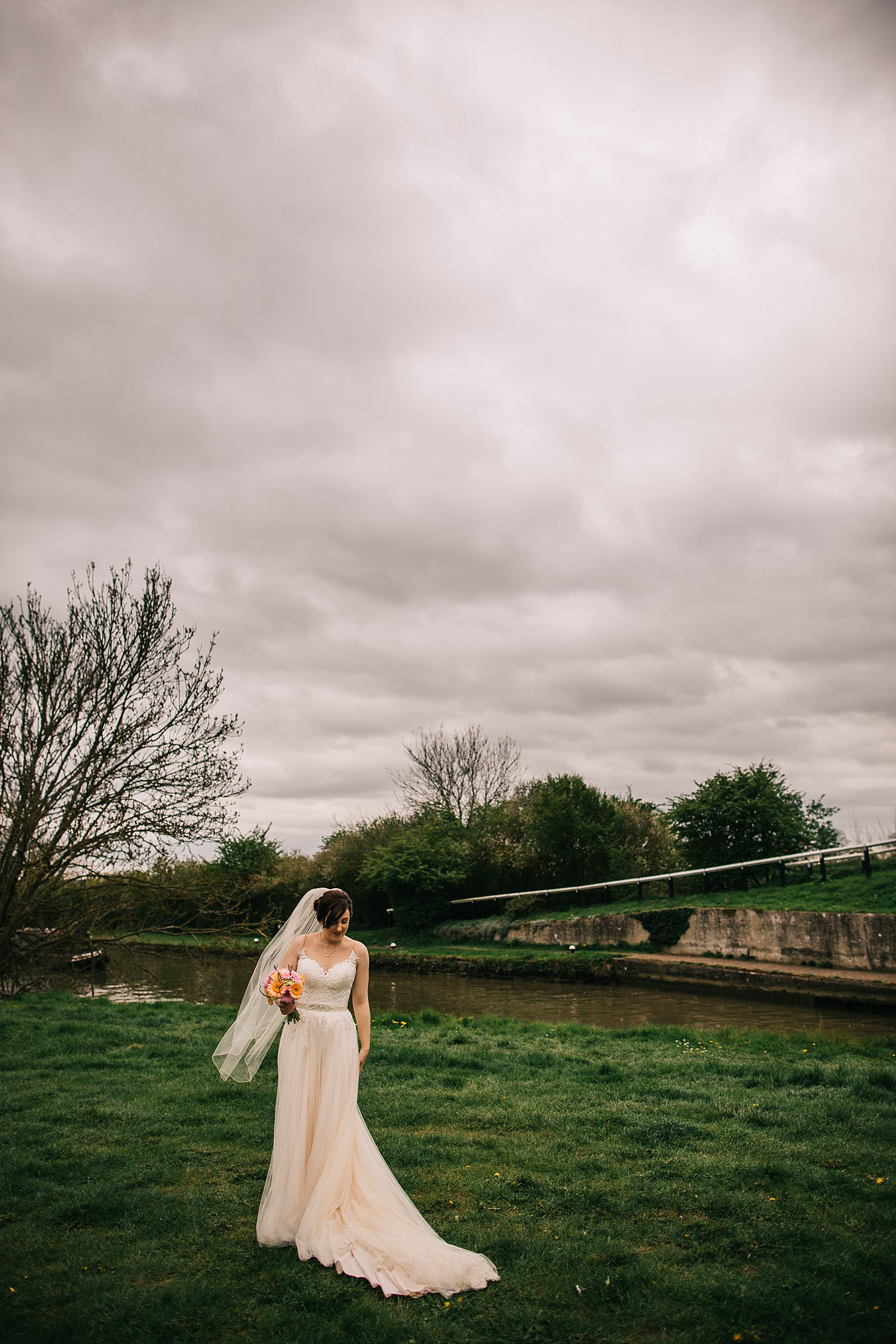 bride standing by a canal being photographed by Northamptonshire wedding photographer