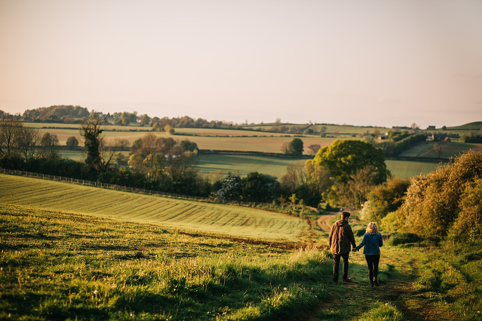 engaged couple walking down the hill overlooking fields