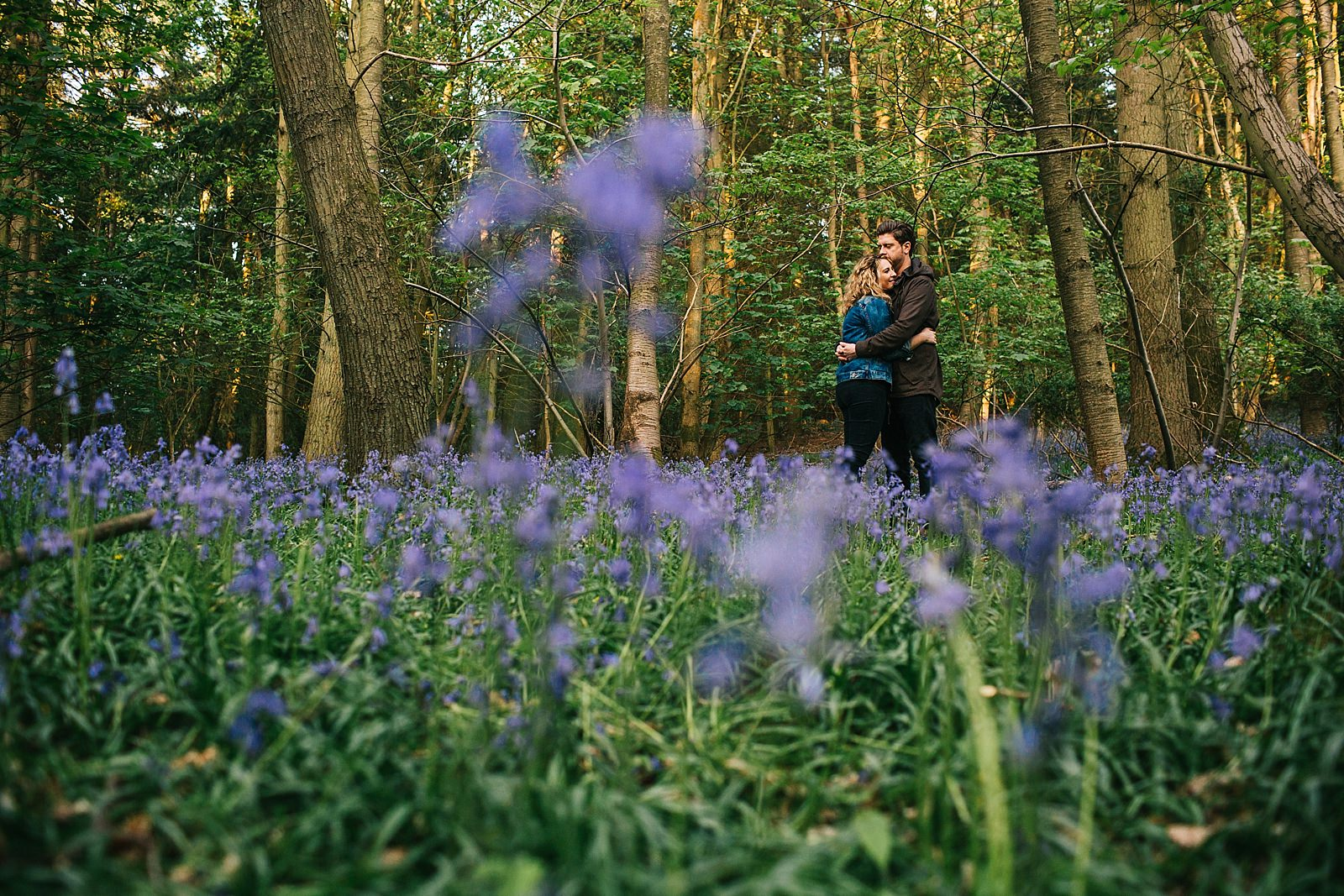 couple standing in bluebells cuddling on their pre wedding photoshoot