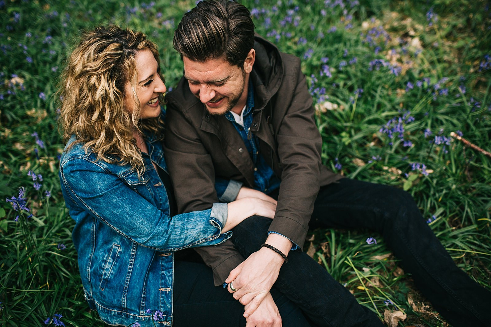 loved up couple laughing and sitting on the grass surrounded by bluebells on their pre wedding photoshoot