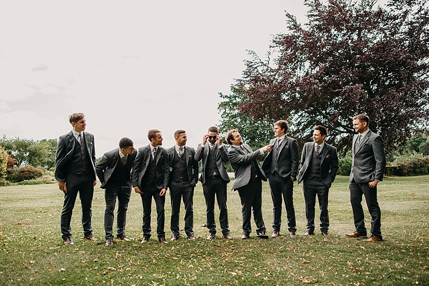 best man and groomsmen standing in line and looking at each other