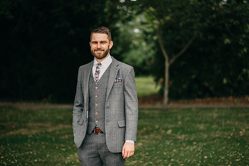 groom standing in the garden with one hand in pocket looking at the camera