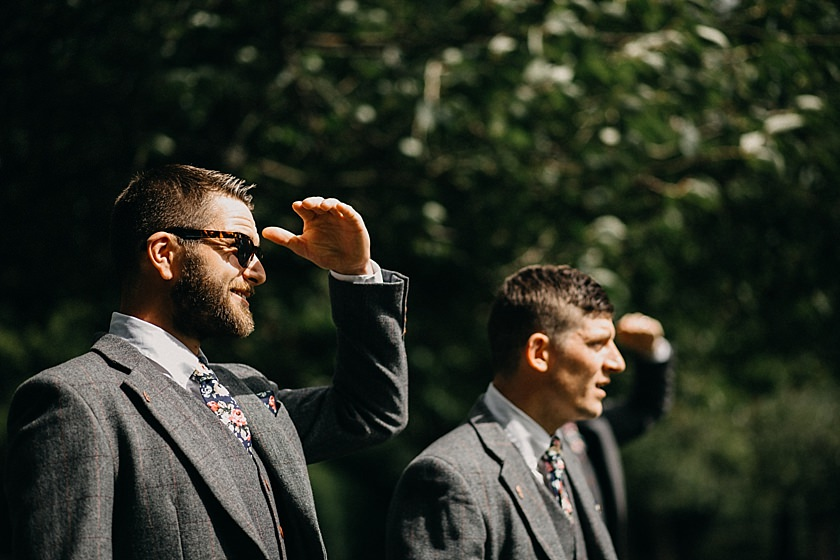 groom and best man looking into the sky and with hand up protecting eyes from sun