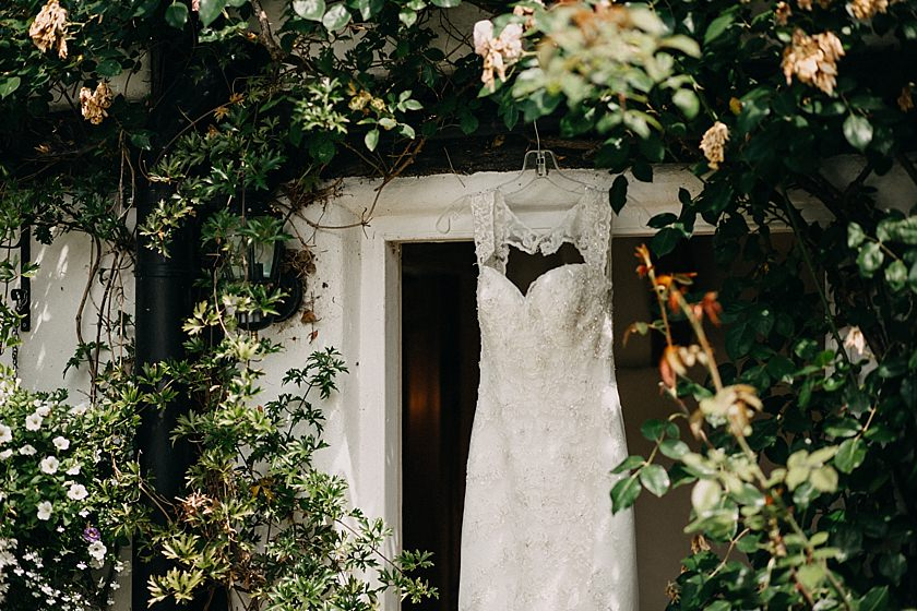 photo of top half of the wedding dress hanging on a door surrounded by roses