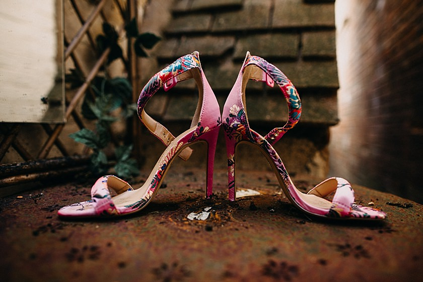 pink wedding shoes standing sideways on a table