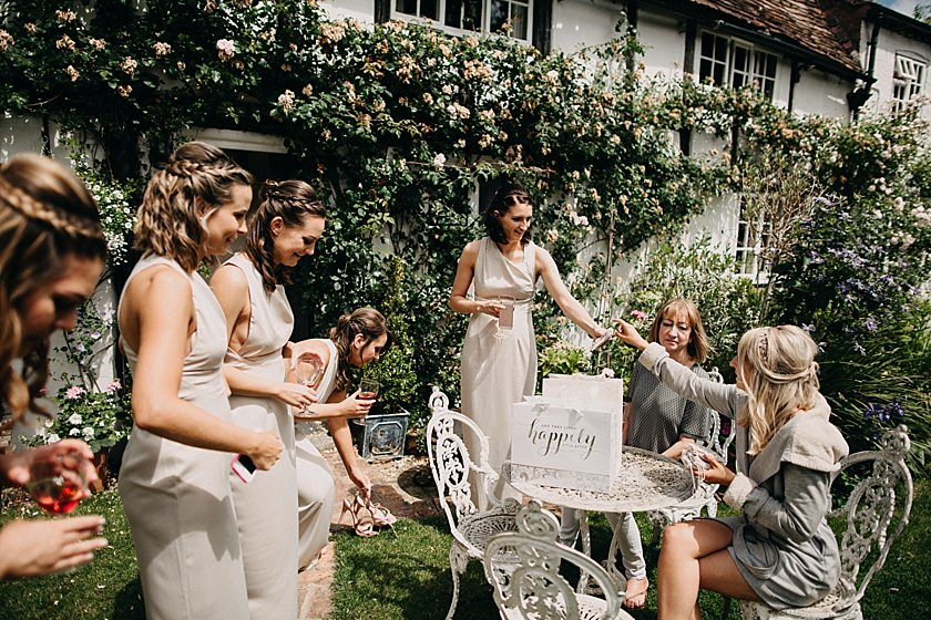 bride sitting in the garden surrounded by bridesmaids giving presents out