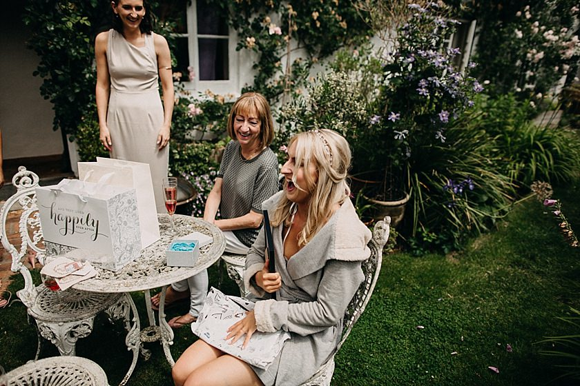 bride shocked sitting on a chair after opening present from bridesmaids
