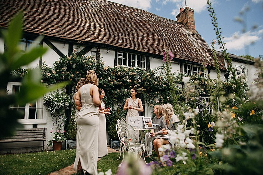 bride and bridesmaids in the garden chatting photographed by Wedding Photographer Buckinghamshire