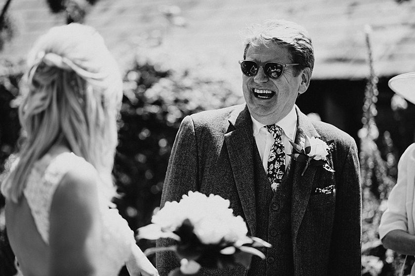 black and white photo of dad wearing sunglasses and smiling at the daughter