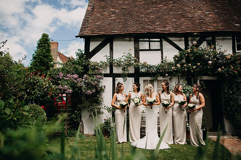 bride and bridesmaids standing outside the cottage
