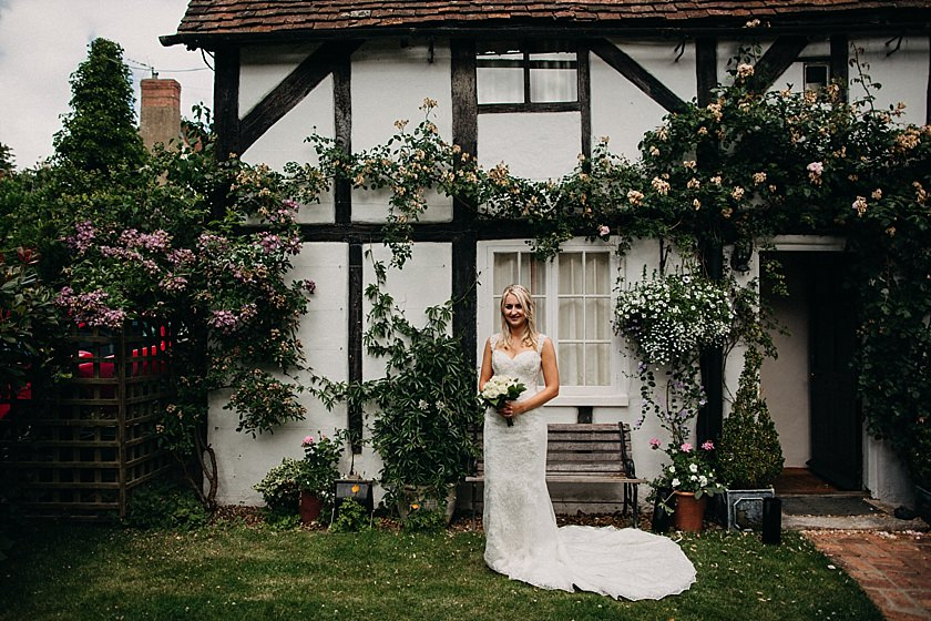 bride standing in front of the cottage with flowers photographed by Wedding Photographer Buckinghamshire