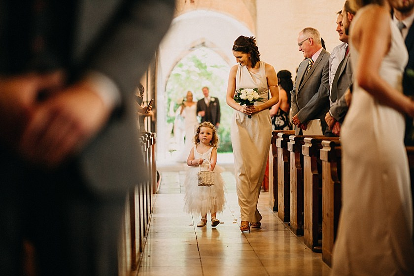 bride and flower girl walking down the aisle