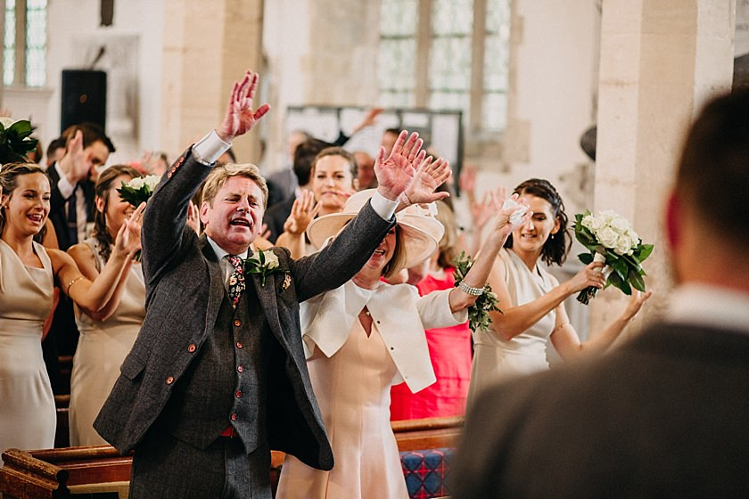 guests signing and have their hands up in the air inside the church