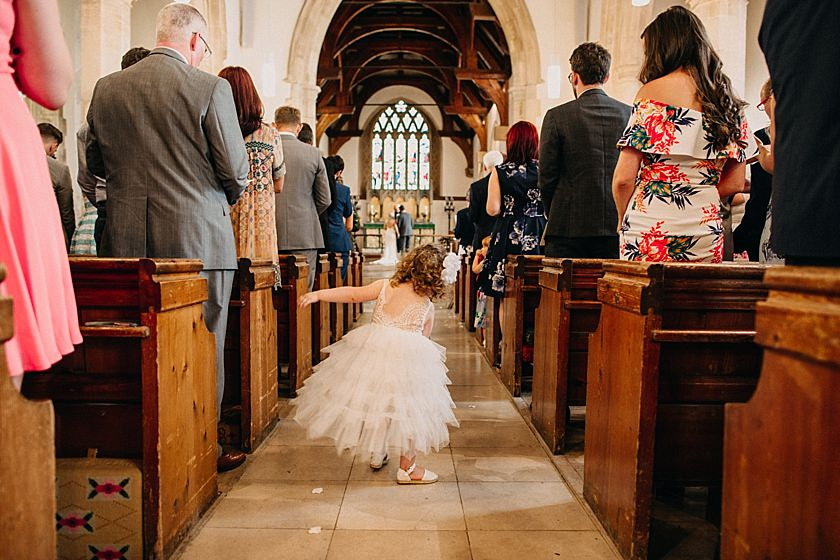 flower girl dancing in the middle of aisle in the church photographed by Wedding Photographer Buckinghamshire