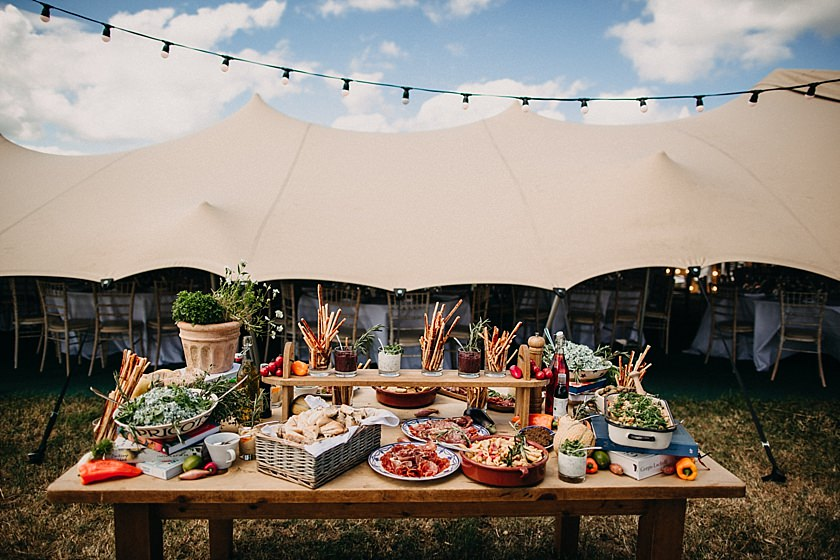 food displayed on a wooden table outside the tent venue