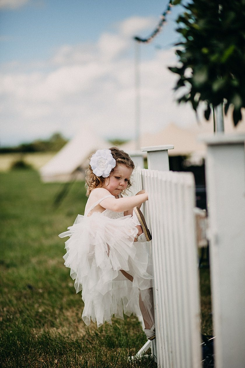 flower girl climbing the fence on her white dress
