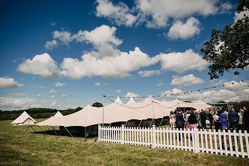 photo of stretch tent on a field with lights and white fence