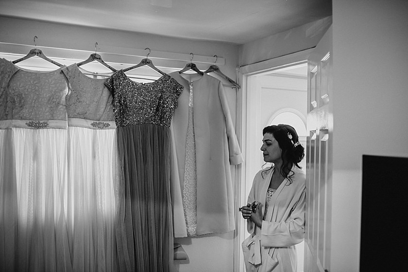bride standing in the door looking at hanging bridesmaid dresses
