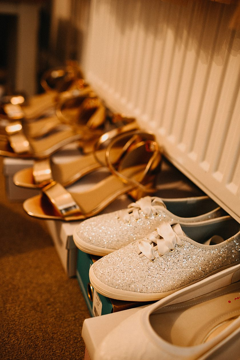 photo of wedding shoes lined up by the radiator on boxes