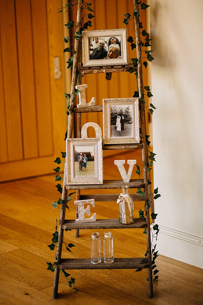 step ladder decorated with ivy and frames with photos