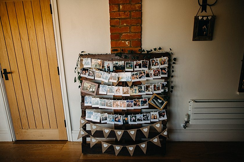 pallet with photos of people hanging on it and decorated with ivy and bunting