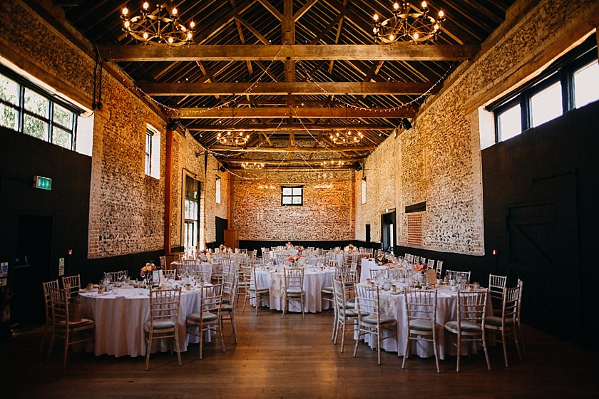 decorated round tables inside barn photographed by Wedding Photography At The Granary Estates