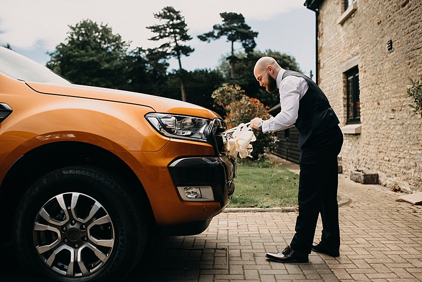 groom putting ribbon on the orange wedding car