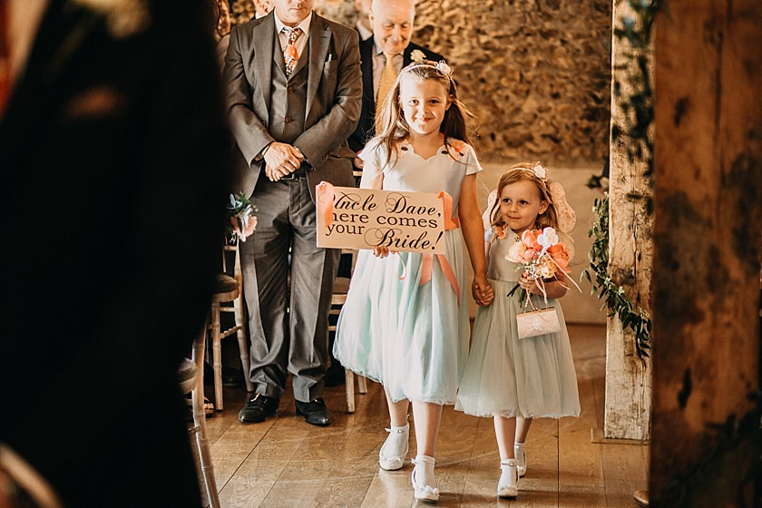 flower girls holding sign and walking down the aisle photographed by Wedding Photography At The Granary Estates