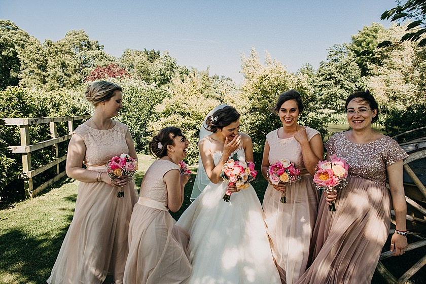 bride and bridesmaids standing next to each other laughing