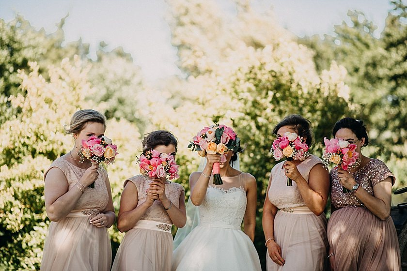 bride and bridesmaids holding flowers to cover their heads